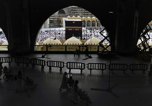 In this Monday, Feb. 24, 2020, photo, Muslim pilgrims circumambulate around the Kaaba, the cubic building at the Grand Mosque, during the minor pilgrimage, known as Umrah in the Muslim holy city of Mecca, Saudi Arabia. Saudi Arabia on Thursday, Feb. 27, 2020, halted forei to the holiest sites in Islam over fears about a new viral epidemic just months ahead of the annual hajj pilgrimage.