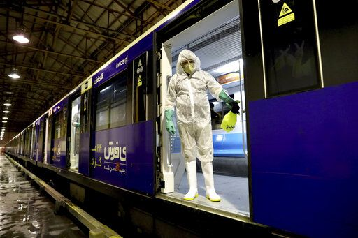 A worker disinfects subway trains against coronavirus in Tehran, Iran, in the early morning of Wednesday, Feb. 26, 2020. Iran's government said Tuesday that more than a dozen people had died nationwide from the new coronavirus, rejecting claims of a much higher death toll of 50 by a lawmaker from the city of Qom that has been at the epicenter of the virus in the country.