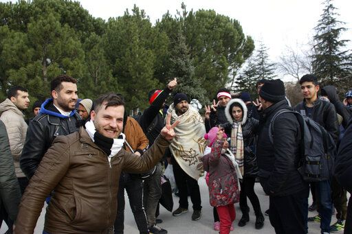 Migrants react as they walk to the border gate of Pazarkule in Edirne, near Turkey-Greece border, early Friday, Feb. 28, 2020. An air strike by Syrian government forces killed scores of Turkish soldiers in northeast Syria, a Turkish official said Friday, marking the largest death toll for Turkey in a single day since it first intervened in Syria in 2016.
