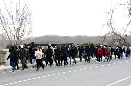 Migrants walk to the border gate of Pazarkule in Edirne, near Turkey-Greece border, early Friday, Feb. 28, 2020. An air strike by Syrian government forces killed scores of Turkish soldiers in northeast Syria, a Turkish official said Friday, marking the largest death toll for Turkey in a single day since it first intervened in Syria in 2016.