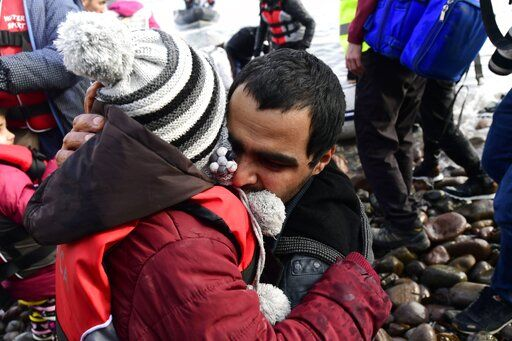 A man hugs a child upon their arrival at the village of Skala Sikaminias, on the Greek island of Lesbos, after crossing the Aegean sea from Turkey, on Friday, Feb. 28, 2020. An air strike by Syrian government forces killed scores of Turkish soldiers in northeast Syria, a Turkish official said Friday, marking the largest death toll for Turkey in a single day since it first intervened in Syria in 2016.