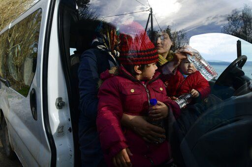Migrants sit inside a vehicle upon their arrival at the village of Skala Sikaminias, on the Greek island of Lesbos, after crossing the Aegean sea from Turkey, on Friday, Feb. 28, 2020. An air strike by Syrian government forces killed scores of Turkish soldiers in northeast Syria, a Turkish official said Friday, marking the largest death toll for Turkey in a single day since it first intervened in Syria in 2016.