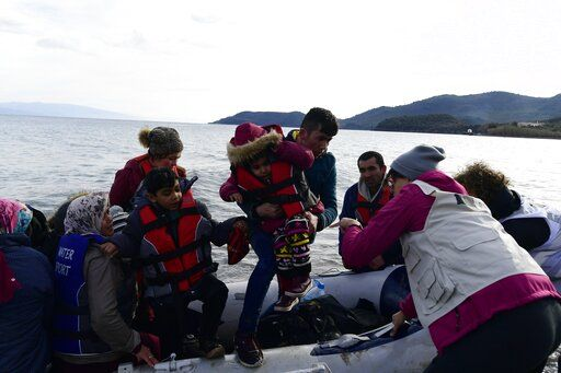 Refugees and migrants arrive with a dinghy at the village of Skala Sikaminias, on the Greek island of Lesbos, after crossing the Aegean sea from Turkey, on Friday, Feb. 28, 2020. An air strike by Syrian government forces killed scores of Turkish soldiers in northeast Syria, a Turkish official said Friday, marking the largest death toll for Turkey in a single day since it first intervened in Syria in 2016.