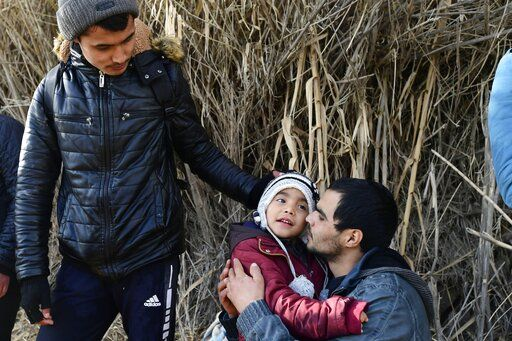 A man hugs a child upon their arrival at the village of Skala Sikaminias, on the Greek island of Lesbos, after crossing the Aegean sea from Turkey with other migrants, on Friday, Feb. 28, 2020. An air strike by Syrian government forces killed scores of Turkish soldiers in northeast Syria, a Turkish official said Friday, marking the largest death toll for Turkey in a single day since it first intervened in Syria in 2016.