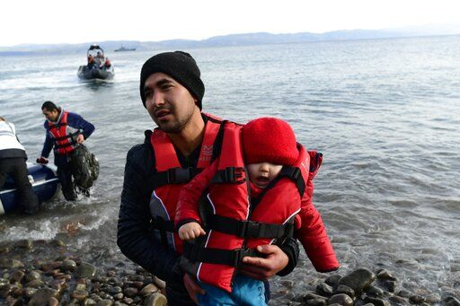 A migrant holds a baby as they arrive at the village of Skala Sikaminias, on the Greek island of Lesbos, after crossing the Aegean sea from Turkey, on Friday, Feb. 28, 2020. An air strike by Syrian government forces killed scores of Turkish soldiers in northeast Syria, a Turkish official said Friday, marking the largest death toll for Turkey in a single day since it first intervened in Syria in 2016.