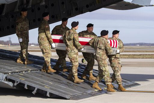 FILE - In this Dec. 25, 2019, file photo, an Army carry team moves a transfer case containing the remains of U.S. Army Sgt. 1st Class Michael Goble at Dover Air Force Base, Del. Goble, a U.S. Special Forces soldier who died in Afghanistan in December 2019.  The U.S. signed a peace agreement with Taliban militants on Saturday, Feb. 29, 2020 aimed at bringing an end to 18 years of bloodshed in Afghanistan and allowing U.S. troops to return home from America's longest war.