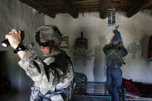 FILE - In this April 18, 2008, file photo, U.S. First Lt. Shane Oravsky, left, of the 101st Airborne Division searches a house with an Afghan police officer in Mandozai, Khost province, Afghanistan. Veterans of America's longest war are torn as the U.S. signs a potentially historic peace accord with the Taliban in Afghanistan. The U.S. signed a peace agreement with Taliban militants on Saturday, Feb. 29, 2020 aimed at bringing an end to 18 years of bloodshed in Afghanistan and allowing U.S. troops to return home from America's longest war.