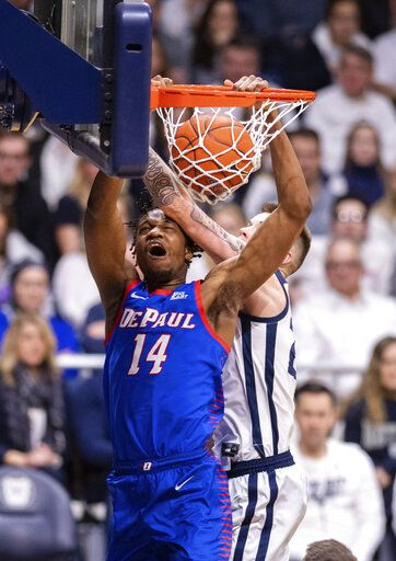 DePaul center Nick Ongenda (14) scores with a slam dunk while Butler forward Sean McDermott, right,makes contact with his head during the second half of an NCAA college basketball game, Saturday, Feb. 29, 2020, in Indianapolis.