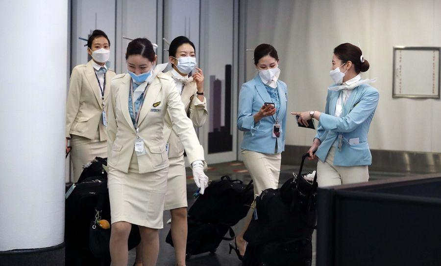 Flight attendants arrive at O'Hare International Airport's Terminal 5 wearing face masks Friday in Chicago. Federal authorities warn that a spread of the coronavirus in the U.S. is imminent.