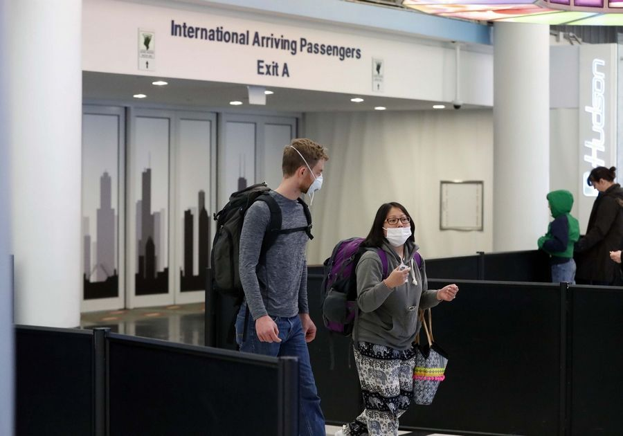 "Jordan McConnell, left, and Sunny Thor, both of Wisconsin, wear face masks at O'Hare International Airport's Terminal 5 Friday after returning from a trip to Thailand. There is risk of contracting the deadly coronavirus in Thailand, federal authorities say, but it ""wasn't really a factor in our decision to go on our trip,"" McConnell said."
