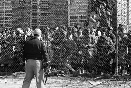 FILE - In this Feb. 4, 1965, file photo, a policeman stands guard outside a fence surrounding the Perry County Jail in Marion, Ala., as arrested civil rights demonstrators chant and sing freedom songs. As the 55th anniversary of the civil rights clash known as Bloody Sunday approaches, townspeople in Alabama want to remind the world that the road to Selma began in a place called Marion.