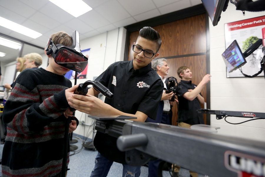 Buffalo Grove High School freshman Angel Alvarez, center, guides Micah Judd, 10, on a virtual welding machine Friday. Northwest Suburban High School District 214 and its Education Foundation celebrated the grand opening Friday of the Saul Ploplys Automation and Technology Lab at Buffalo Grove High School. Micah is Ploplys' grandson.