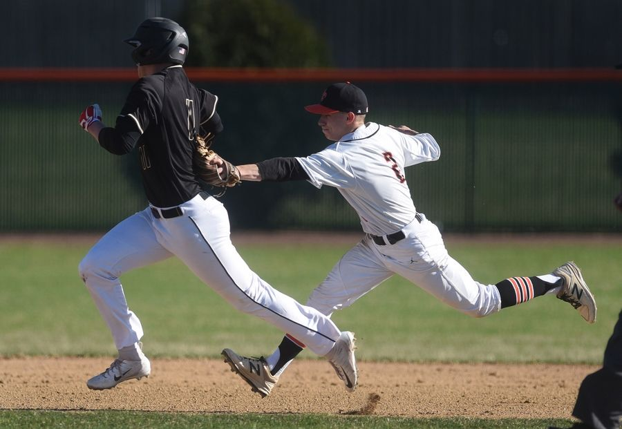 Paul Valade/pvalade@dailyherald.comSt. Charles East's Clay Conn (2) tags out Glenbard North's Mike Wellman on a rundown between second and third base during Monday's baseball game in St. Charles.