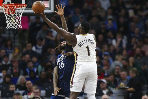 New Orleans Pelicans' Zion Williamson (1) shoots over Minnesota Timberwolves' James Johnson in the first half of an NBA basketball game Sunday, March 8, 2020, in Minneapolis.