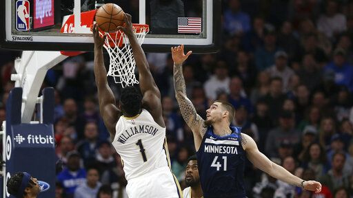 New Orleans Pelicans' Zion Williamson scores against Minnesota Timberwolves' Juancho Hernangomez in the first half of an NBA basketball game, Sunday, March 8, 2020, in Minneapolis.