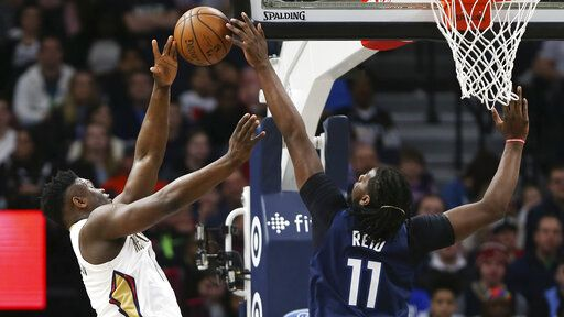 Minnesota Timberwolves' Naz Reid blocks a shot-attempt by New Orleans Pelicans' Zion Williamson in the first half of an NBA basketball game Sunday, March 8, 2020, in Minneapolis.