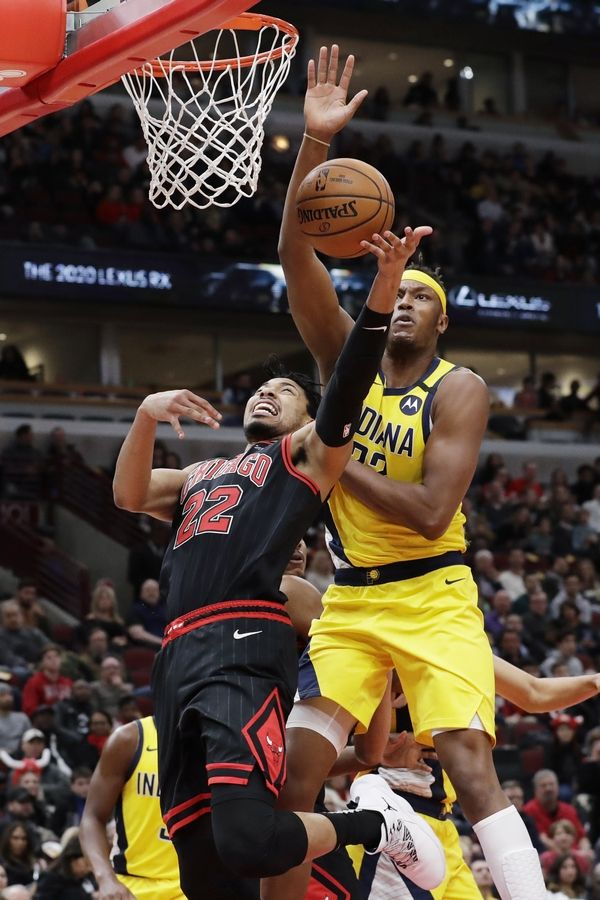 Chicago Bulls forward Otto Porter Jr., left, shoots against Indiana Pacers' Myles Turner during the second half of an NBA basketball game in Chicago, Friday, March 6, 2020. The Pacers won 108-102.