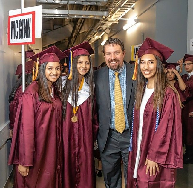 Schaumburg High School science teacher and soccer coach Jason Georgacakis celebrates with Class of 2019 graduates, from left, Shivani Patel, Krupa Patel and Mona Pudasaini, during commencement ceremonies last year at the Sears Centre Arena.