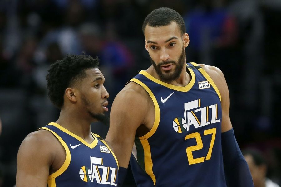 FILE -- In this Saturday, March 7, 2020, file photo, Utah Jazz center Rudy Gobert (27) talks with guard Donovan Mitchell, left, during the second half of an NBA basketball game against the Detroit Pistons, in Detroit. Both players have tested positive for the coronavirus. Gobert's test result forced the NBA to suspend the season.
