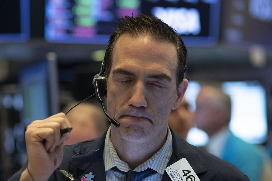 Stock trader Gregory Rowe works Wednesday at the New York Stock Exchange in New York. Global stock markets have sunk in a third day of wild price swings after President Donald Trump promised to prop up the U.S. economy through the coronavirus outbreak.
