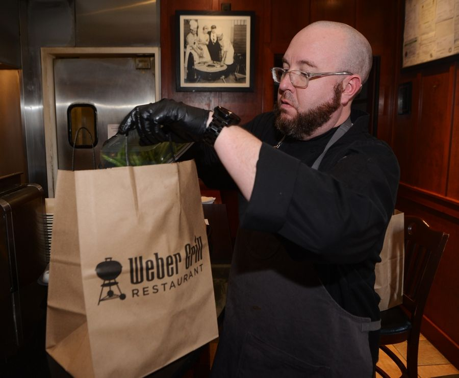 Weber Grill Corporate Chef Matt McCormick packs up carryout meals at the Schaumburg restaurant.