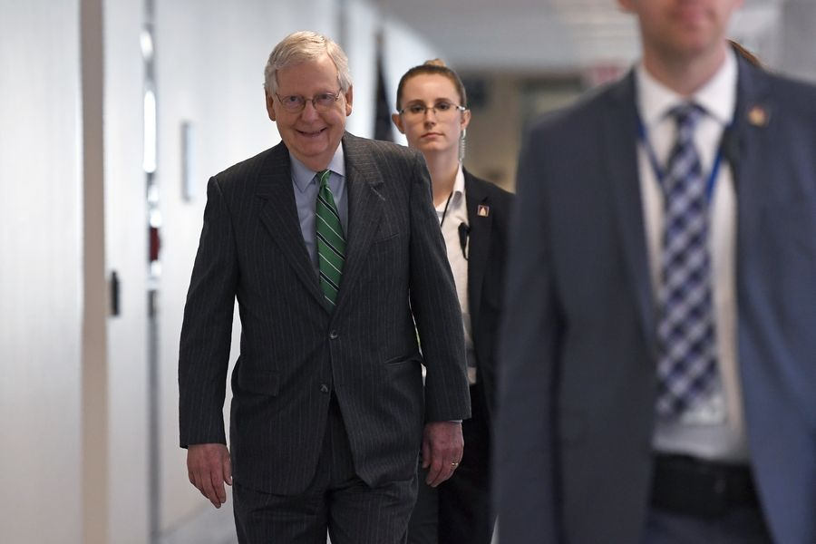 Senate Majority Leader Mitch McConnell of Ky., walk to attend a Republican policy lunch on Capitol Hill in Washington, Thursday, March 19, 2020.
