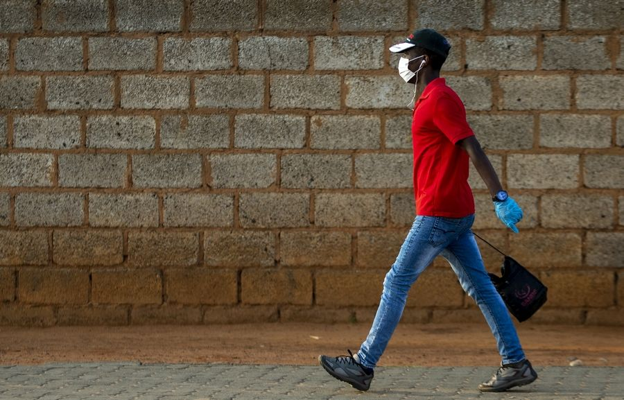 A man wearing a surgical mask and gloves to protect himself from the coronavirus walks Thursday on a street in Soweto, South Africa. For most people the virus causes only mild or moderate symptoms. For others it can cause more severe illness, especially in older adults and people with existing health problems.