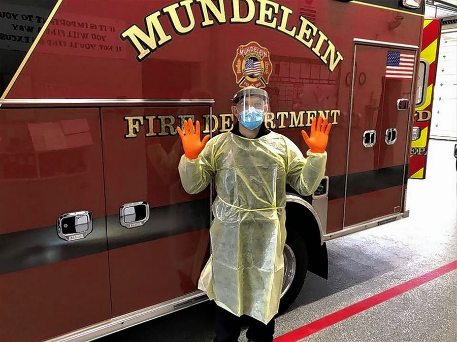 Mundelein firefighter/paramedic Brad Sashko demonstrates wearing a disposable gown, gloves, eye protection, and a mask with face shield.