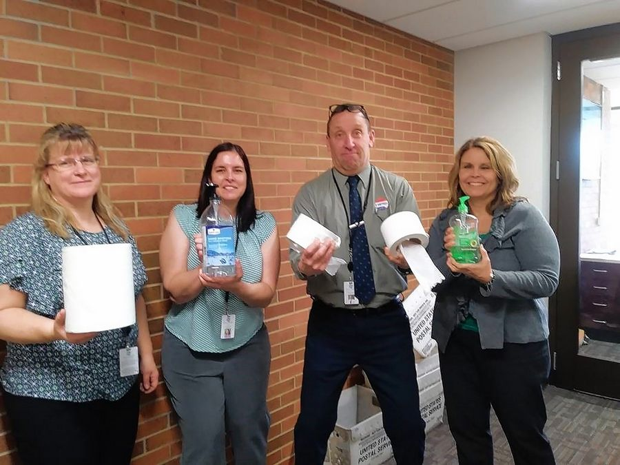 From left to right, Andrea Granias, Suzanne Thorson, George Sullivan, and Sheryl Donovan are using sanitizer and paper rolls as hand weights.