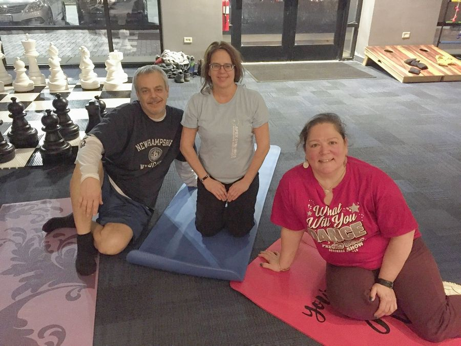 Eric Wahl, Michelle Sprainis, and Elizabeth Olcese are taking a break during a yoga class hosted at Athleta at Deer Park Town Center.