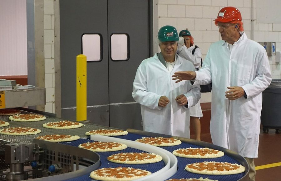 A Richelieu Foods Inc. employee explains the process for making pizzas to former Gov. Bruce Rauner when the Wheeling manufacturing plant opened in 2016.