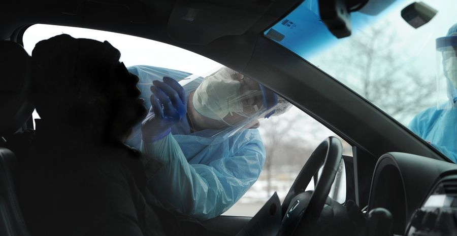Pete Schorr, physician assistant for Edward-Elmhurst Hospital, swabs the nose of a drive-up patient, who will be tested for the COVID-19 virus, in the parking lot at the Edward-Elmhurst Health Corporate Center in Warrenville on Monday.