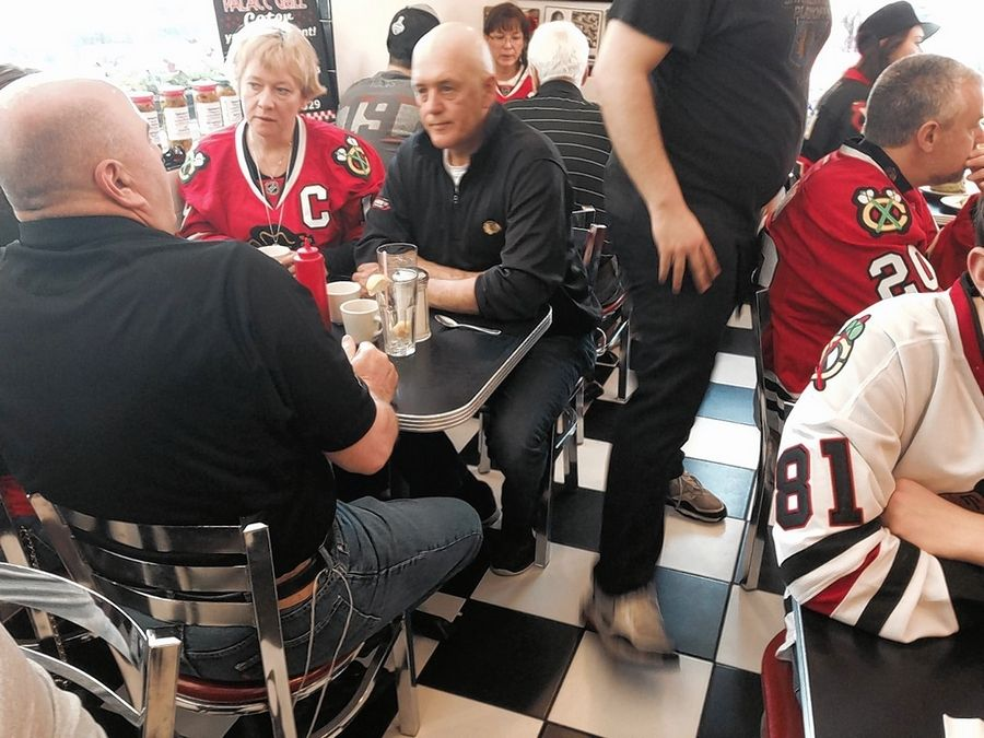 Patrick Kane Sr. (with his back to the camera) and Bryan Toews are tied to their chairs at the Palace Grill.