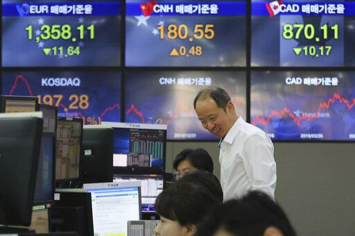 A currency trader smiles at the foreign exchange dealing room of the KEB Hana Bank headquarters in Seoul, South Korea, Wednesday, March 25, 2020. Shares have advanced in Asia after the Dow Jones Industrial Average surged to its best day since 1933 as Congress and the White House neared a deal to inject nearly $2 trillion of aid into an economy ravaged by the coronavirus.