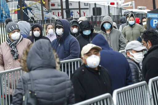 Patients wear personal protective equipment while maintaining social distancing as they wait in line for a COVID-19 test at Elmhurst Hospital Center, Wednesday, March 25, 2020, in New York. Gov. Andrew Cuomo sounded his most dire warning yet about the coronavirus pandemic Tuesday, saying the infection rate in New York is accelerating and the state could be as close as two weeks away from a crisis that sees 40,000 people in intensive care. Such a surge would overwhelm hospitals, which now have just 3,000 intensive care unit beds statewide.