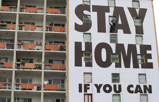 A billboard is installed on an apartment building in Cape Town, South Africa, Wednesday, March 25, 2020, before the country of 57 million people, will go into a nationwide lockdown for 21 days from Thursday to fight the spread of the new coronavirus. The new coronavirus causes mild or moderate symptoms for most people, but for some, especially older adults and people with existing health problems, it can cause more severe illness or death.