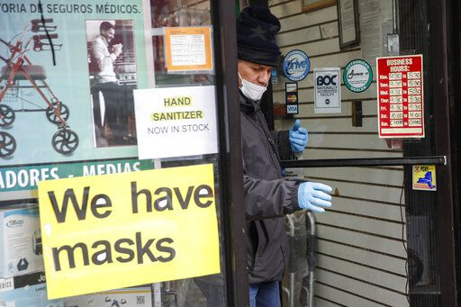 A customer leaves a shop advertising personal protective equipment near Elmhurst Hospital Center, Wednesday, March 25, 2020, in New York. Gov. Andrew Cuomo sounded his most dire warning yet about the coronavirus pandemic Tuesday, saying the infection rate in New York is accelerating and the state could be as close as two weeks away from a crisis that sees 40,000 people in intensive care. Such a surge would overwhelm hospitals, which now have just 3,000 intensive care unit beds statewide.