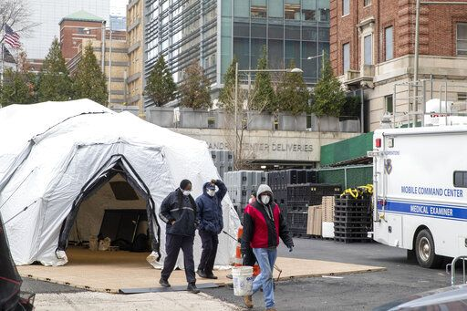 Medical Examiner personnel and construction workers are seen at the site of a makeshift morgue being built in New York, Wednesday, March 25, 2020. The number of people hospitalized with COVID-19 in New York climbed to 3,800, with close to 900 in intensive care, with the peak of the outbreak weeks away, Gov. Andrew Cuomo said Wednesday. The new coronavirus causes mild or moderate symptoms for most people, but for some, especially older adults and people with existing health problems, it can cause more severe illness or death.