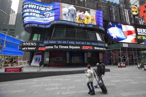 A couple looks at the ABC News video screen showing coverage of a coronavirus outbreak in Woodbridge, N.J., Wednesday, March 25, 2020, in New York's Times Square. The number of people hospitalized with COVID-19 in New York climbed to 3,800, with close to 900 in intensive care, with the peak of the outbreak weeks away, Gov. Andrew Cuomo said Wednesday. The new coronavirus causes mild or moderate symptoms for most people, but for some, especially older adults and people with existing health problems, it can cause more severe illness or death.