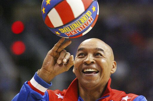 "FILE - In this Jan. 9, 2008, file photo, the Harlem Globetrotters' Fred ""Curly"" Neal performs during a timeout in the second quarter in an NBA basketball game between the Indiana Pacers and the Phoenix Suns in Phoenix. Neal, the dribbling wizard who entertained millions with the Harlem Globetrotters for parts of three decades, has died the Globetrotters announced Thursday, March 26, 2020. He was 77. Neal played for the Globetrotters from 1963-85, appearing in more than 6,000 games in 97 countries for the exhibition team known for its combination of comedy and athleticism."