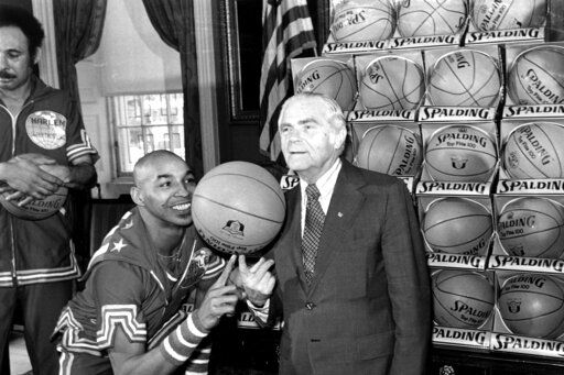 "FILE - In this Feb. 15, 1977, file photo, the Harlem Globetrotters' Fred ""Curly"" Neal of shows New York City Mayor Abe Beame the art of balancing a basketball on a finger during ceremony at City Hall. Neal, the dribbling wizard who entertained millions with the Harlem Globetrotters for parts of three decades, has died the Globetrotters announced Thursday, March 26, 2020. He was 77. Neal played for the Globetrotters from 1963-85, appearing in more than 6,000 games in 97 countries for the exhibition team known for its combination of comedy and athleticism."