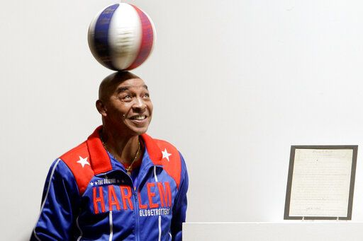 "FILE - In this Dec. 10, 2010, file photo, Harlem Globetrotters Fred ""Curly"" Neal spins a ball on his head prior to the bidding for the Naismith Rules, the original rules for basketball, framed at right, at Sotheby's in New York. Neal, the dribbling wizard who entertained millions with the Harlem Globetrotters for parts of three decades, has died the Globetrotters announced Thursday, March 26, 2020. He was 77. Neal played for the Globetrotters from 1963-85, appearing in more than 6,000 games in 97 countries for the exhibition team known for its combination of comedy and athleticism."
