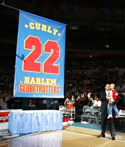 "FILE - In this Feb. 15, 2008, file photo, Harlem Globetrotters' Fred ""Curly"" Neal looks on with his grandson Jaden Neal-Roberts as his No. 22 is retired by the world renowned Harlem Globetrotters at Madison Square Garden in New York. Neal, the dribbling wizard who entertained millions with the Harlem Globetrotters for parts of three decades, has died the Globetrotters announced Thursday, March 26, 2020. He was 77. Neal played for the Globetrotters from 1963-85, appearing in more than 6,000 games in 97 countries for the exhibition team known for its combination of comedy and athleticism."