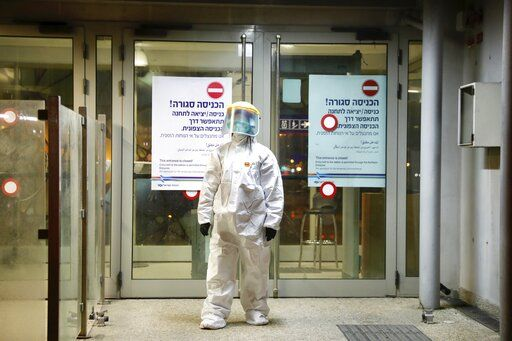 '�A municipality worker blocks the door as a firefighter sprays disinfectant as a precaution'� against the coronavirus at the Moshe Dayan Railway Station in Rishon LeTsiyon, Israel, Sunday, March 22, 2020.