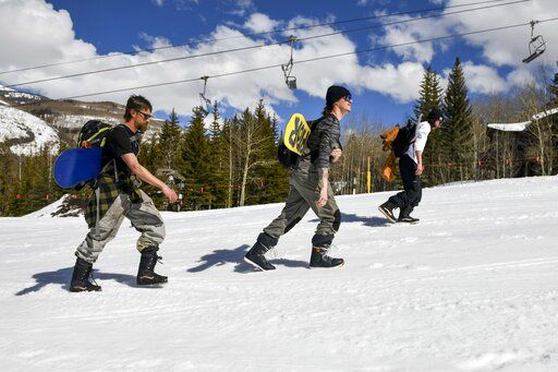 "This Tuesday, March 24, 2020 photo shows snowboarders, from left, Colin Tabb, Tyler Alvarez and Shaun Carroll, determined to get in a run, hike up an empty ski run past a closed chair lift at Vail, Colo., after Vail Ski Resort closed for the season amid the COVID-19 pandemic. 'œToday it's desolate. It's a ghost town,"" said Tabb, a Vail resident and snowboarder. 'œUsually we are fighting lift lines and we are doing our thing still, but it's a complete ghost town.'�"