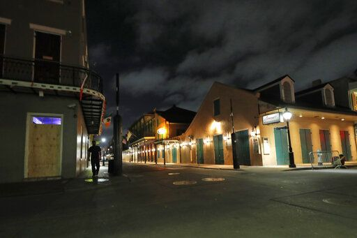 FILE - In this Thursday, March 19, 2020, file photo, a view of the nearly deserted Bourbon Street, which is normally bustling with tourists and revelers, is seen in the French Quarter of New Orleans. Like many cities around the country, New Orleans is currently under a shelter-in-place order as it grapples with a growing number of coronavirus cases. In Louisiana, Gov. John Bel Edwards has repeatedly sounded the alarm about how Louisiana has the third-highest rate of confirmed virus cases per capita while at the same time noting the difficulty of the small state getting supplies.
