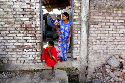 Women look out a door in a neighborhood mostly inhabited by daily wage laborers in Prayagraj, India , Thursday, March 26, 2020. Some of India's legions of poor and people suddenly thrown out of work by a nationwide stay-at-home order began receiving aid distribution Thursday, as both the public and private sector work to blunt the impact of efforts to curb the coronavirus pandemic. Untold numbers of them are now out of work and many families have been left struggling to eat.