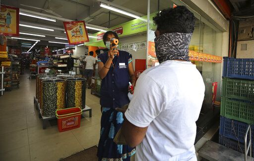 An Indian attendant checks the temperature of a customer before allowing him inside a supermarket during lockdown in Bangalore, India, Thursday, March 26, 2020. The unprecedented lockdown keeping India's 1.3 billion people at home for all but essential trips to places like supermarkets or pharmacies is meant to keep virus cases from surging above the 553 already recorded and overwhelming an already strained health care system. The new coronavirus causes mild or moderate symptoms for most people, but for some, especially older adults and people with existing health problems, it can cause more severe illness or death.