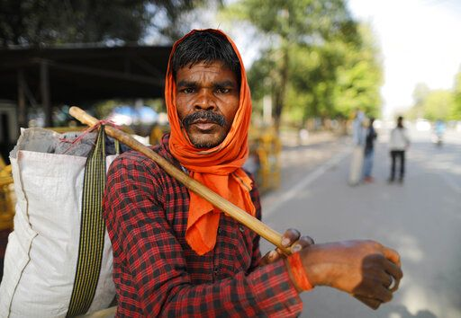 Hiralal, a daily wage laborer, leaves for his village as the city comes under lockdown in Prayagraj, India , Thursday, March 26, 2020. Some of India's legions of poor and people suddenly thrown out of work by a nationwide stay-at-home order began receiving aid distribution Thursday, as both the public and private sector work to blunt the impact of efforts to curb the coronavirus pandemic. Untold numbers of them are now out of work and many families have been left struggling to eat.