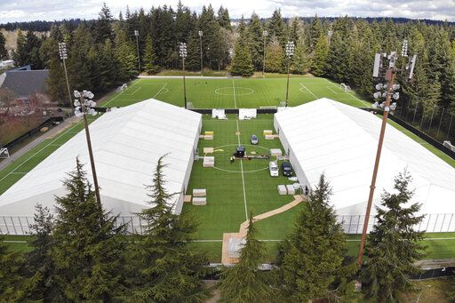 In this photo taken Tuesday, March 24, 2020, two massive temporary buildings meant for use as a field hospital for coronavirus patients stand together on a soccer field in the Seattle suburb of Shoreline, Wash. With U.S. hospital capacity stretched thin, hospitals around the country are scrambling to find space for a coming flood of COVID-19 patients, opening older closed hospitals and repurposing other buildings.